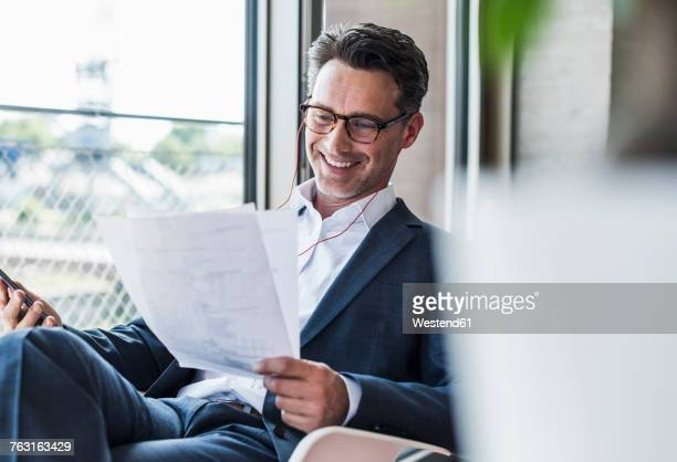 Smiling businessman on the phone reading documents