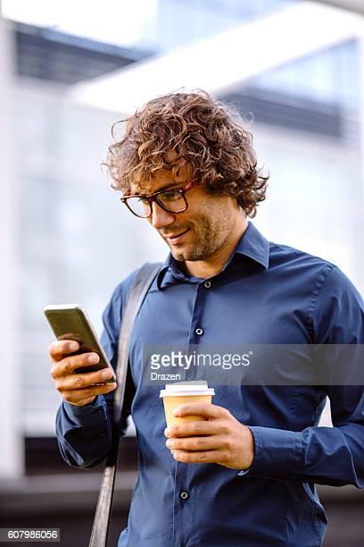 Smiling businessman playing mobile game while walking on street