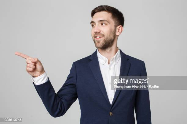smiling businessman pointing against gray background - pointing stock pictures, royalty-free photos & images