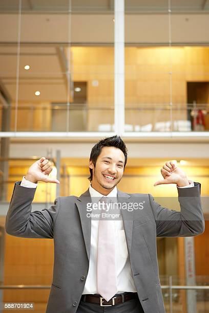 smiling businessman pointing at himself - oliver eltinger stock-fotos und bilder