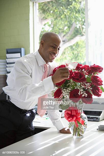 smiling businessman reading greeting card on vase of flowers - valentines african american stock pictures, royalty-free photos & images
