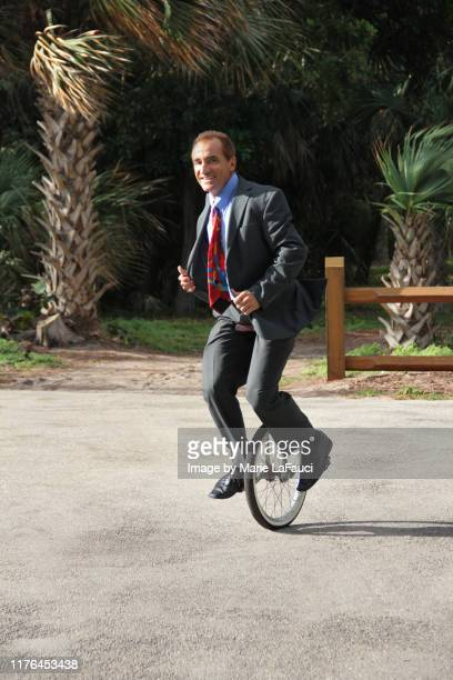 smiling businessman riding a unicycle - fauci stock pictures, royalty-free photos & images