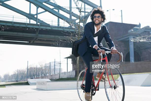 smiling businessman riding bicycle at riverside bridge - black suit stock pictures, royalty-free photos & images