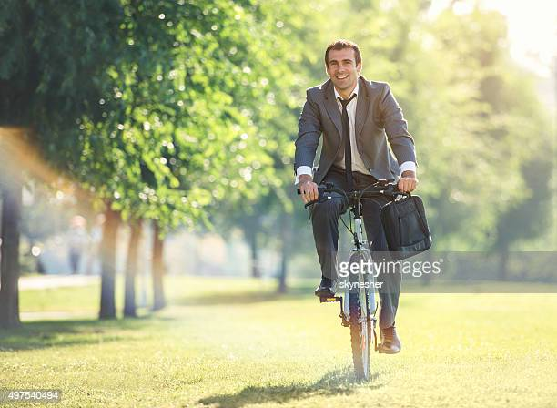 Smiling businessman riding bicycle in the park.