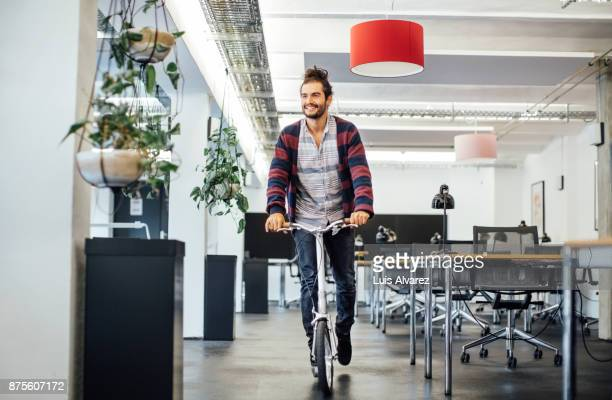 Smiling businessman riding push scooter