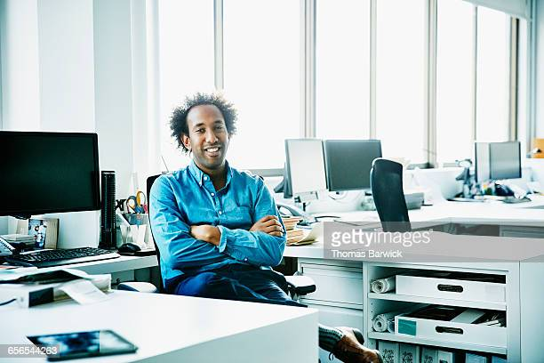 Smiling businessman seated at office workstation