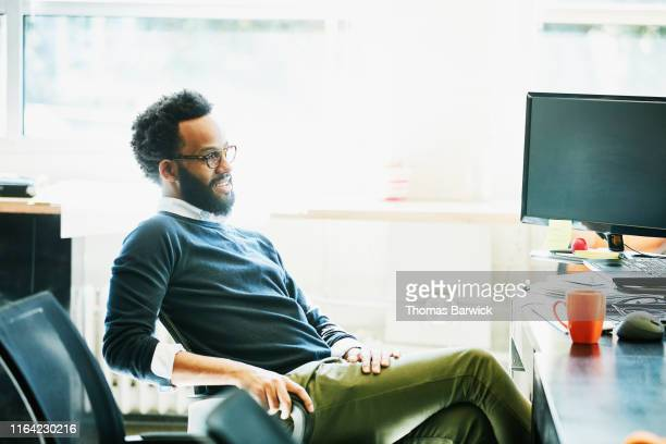 smiling businessman seated at workstation in office - 足を組む ストックフォトと画像