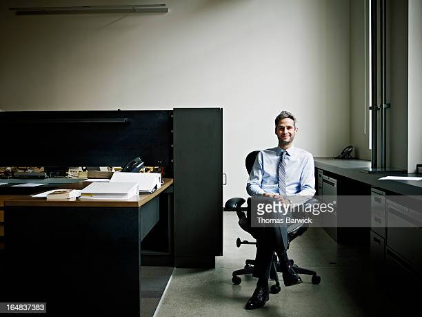 smiling businessman seated in chair in office - 足を組む ストックフォトと画像