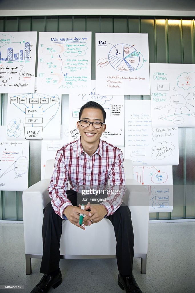 Smiling businessman seated with charts : Stock Photo