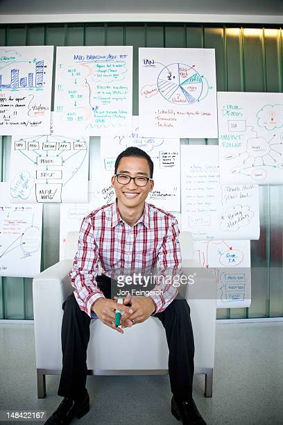 Smiling businessman seated with charts