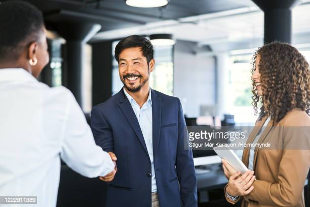 smiling businessman shaking hands with colleague - handshake stock pictures, royalty-free photos & images