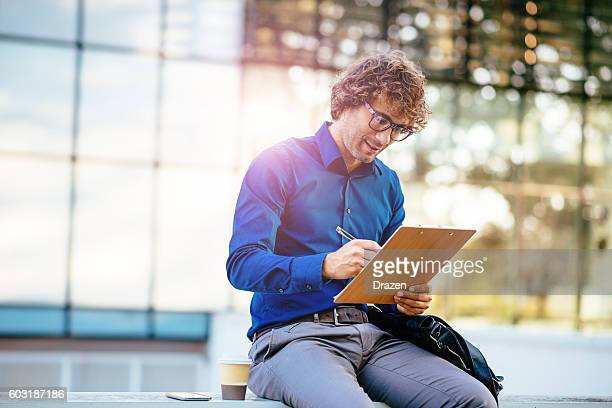 Smiling businessman signing project proposal before sending it