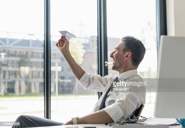 Smiling businessman sitting at desk in his office looking at paper plane