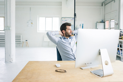 Smiling businessman sitting at desk in office having a break - gettyimageskorea