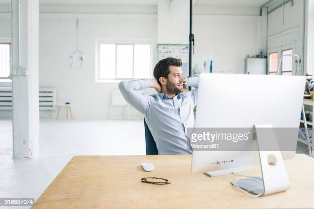 Smiling businessman sitting at desk in office having a break