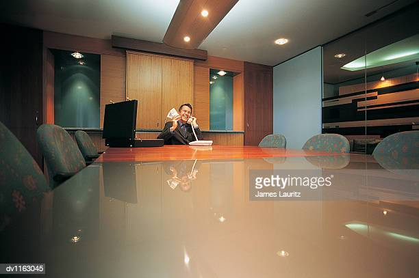 Smiling Businessman Sitting Behind a Table Holding a Bundle of Money