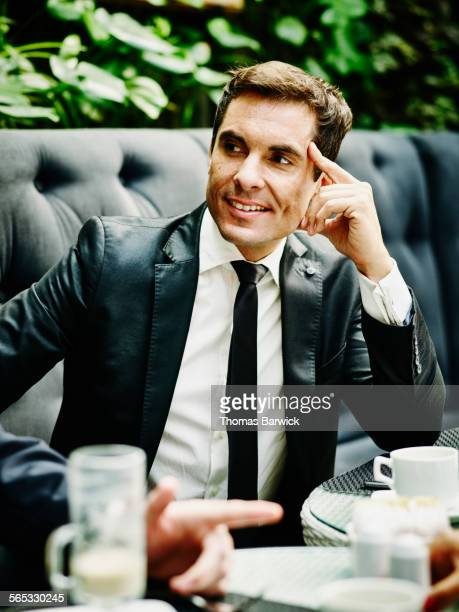 Smiling businessman sitting in lunch meeting