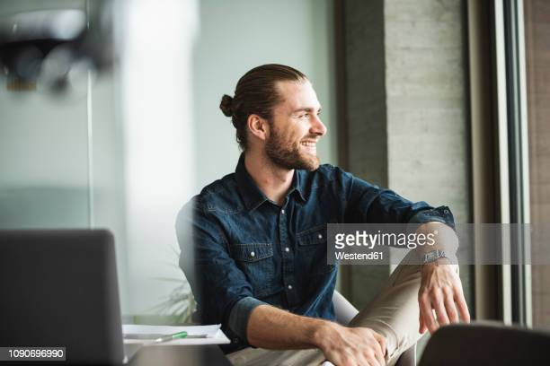 smiling businessman sitting in office looking out of window - おだんごヘア ストックフォトと画像