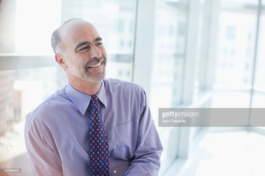 Smiling businessman sitting in office : Stock Photo