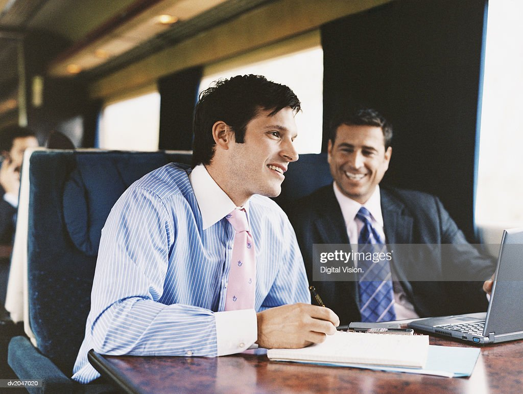 Smiling Businessman Sitting on a Passenger Train and Listening to a Discussion : Stock Photo