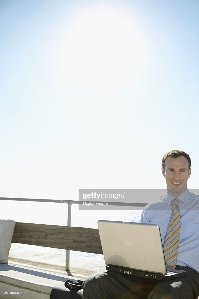 Smiling Businessman Sitting on a Waterfront With a Laptop : Stock Photo