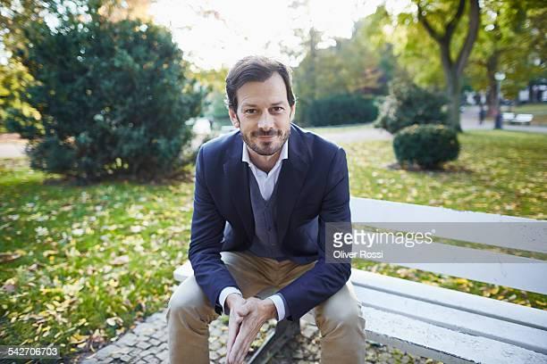 smiling businessman sitting on bench in park - ジャケット ストックフォトと画像
