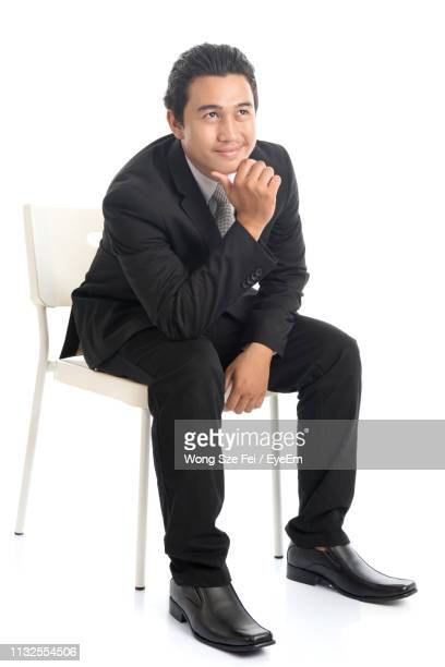 smiling businessman sitting on chair against white background - 顎に手をやる ストックフォトと画像