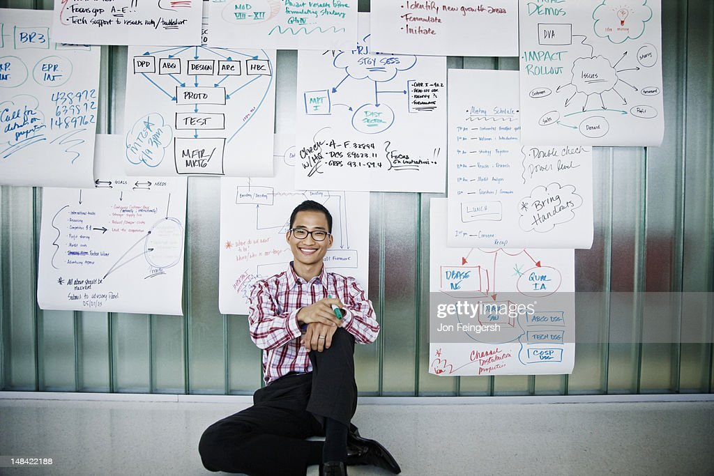 Smiling businessman sitting on floor : Stock Photo