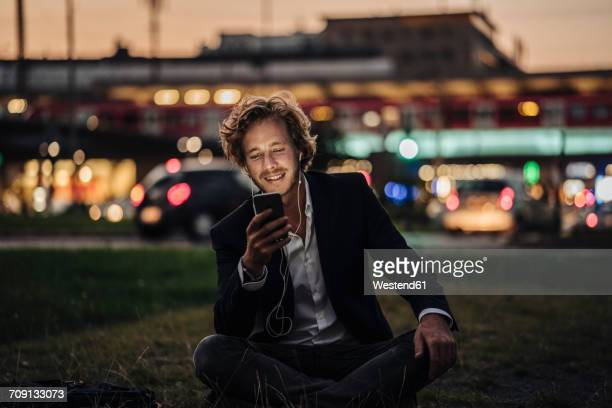 smiling businessman sitting on meadow at dusk with cell phone and earphones - dämmerung stock-fotos und bilder