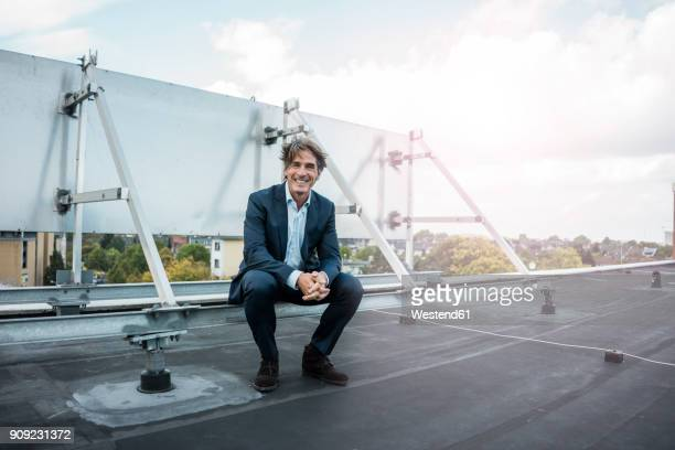 smiling businessman sitting on roof - anzug stock-fotos und bilder