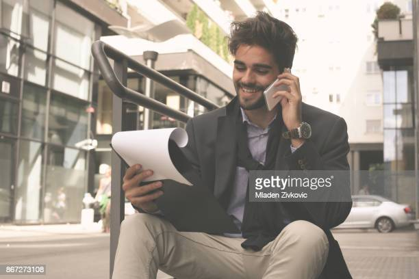 Smiling businessman sitting on stairs and talking on mobile phone.
