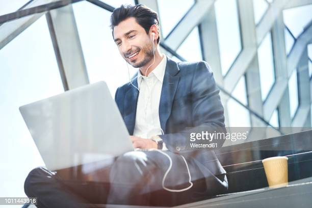smiling businessman sitting on stairs wearing earphones and using laptop - human age stock pictures, royalty-free photos & images