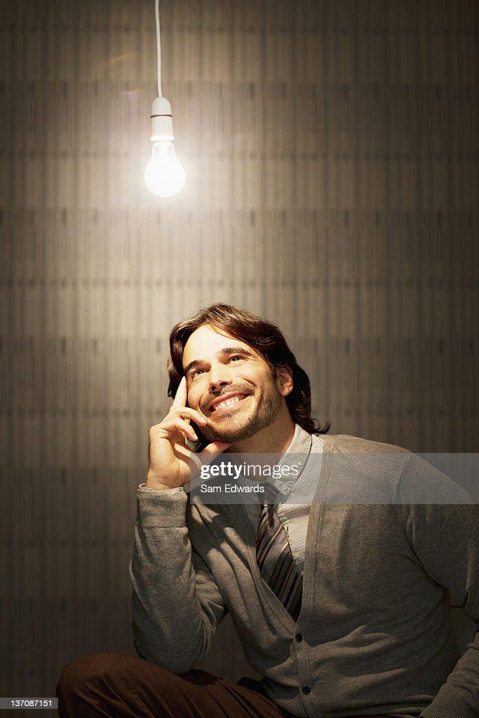 Smiling businessman sitting under illuminated light bulb : Stock Photo