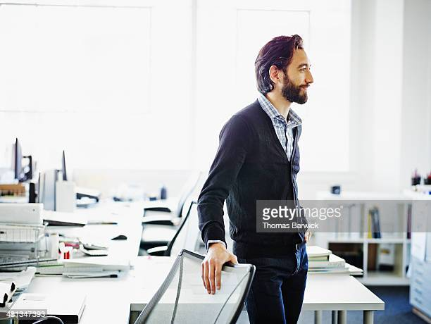 Smiling businessman standing at workstation