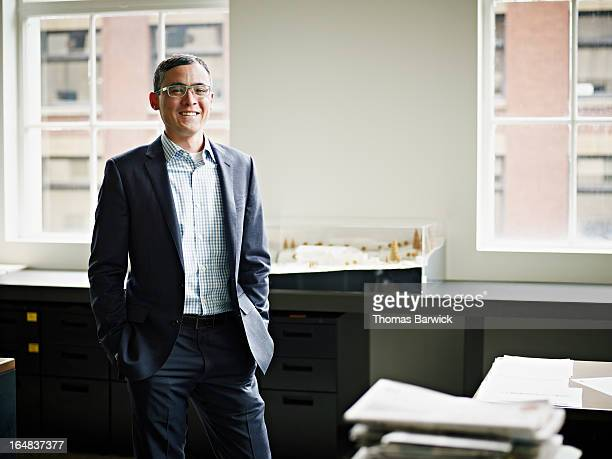 Smiling businessman standing in architects office