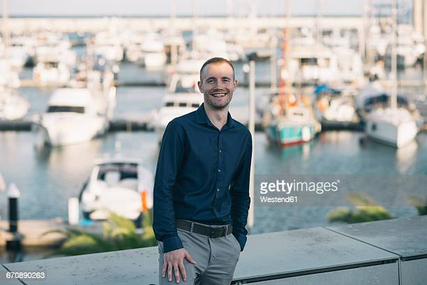 Smiling businessman standing in front of harbour