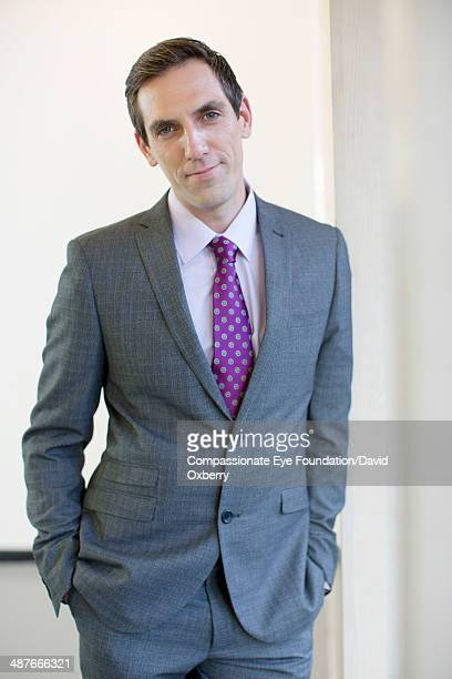 smiling businessman standing in office hallway - head cocked stock pictures, royalty-free photos & images