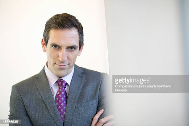 Smiling businessman standing in office hallway