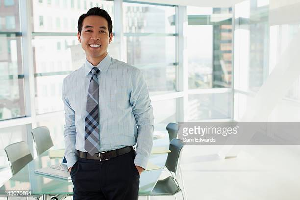 smiling businessman standing in office - asian and indian ethnicities stock pictures, royalty-free photos & images