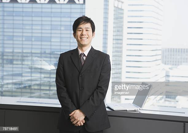 Smiling businessman standing near by the window