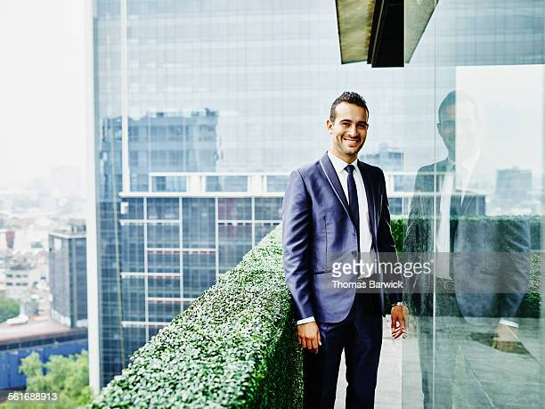 smiling businessman standing on office terrace - handsome mexican men stock pictures, royalty-free photos & images