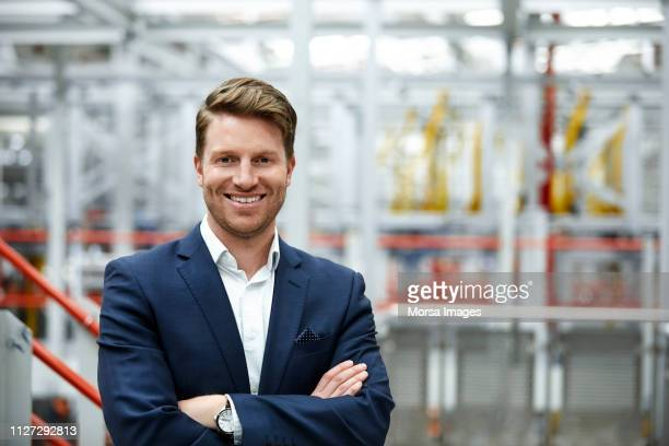 smiling businessman standing with arms crossed - blue suit stock pictures, royalty-free photos & images