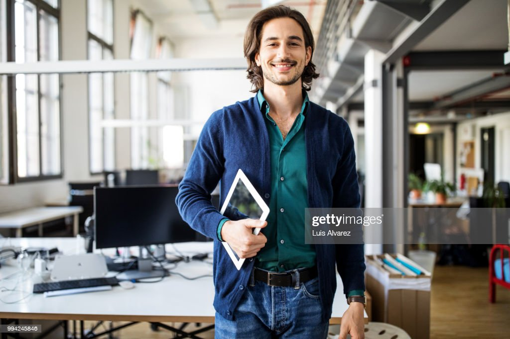 Smiling businessman standing with digital tablet : Photo
