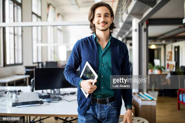 smiling businessman standing with digital tablet - bureau ameublement photos et images de collection