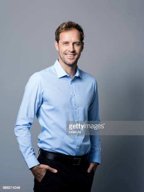 smiling businessman standing with hands in pockets - three quarter length stock pictures, royalty-free photos & images