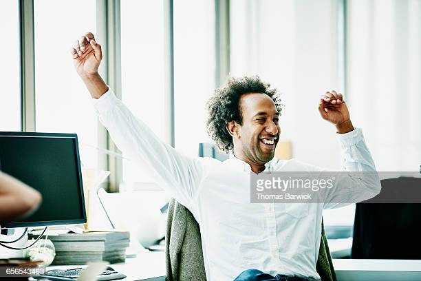 smiling businessman stretching during meeting - image stock pictures, royalty-free photos & images