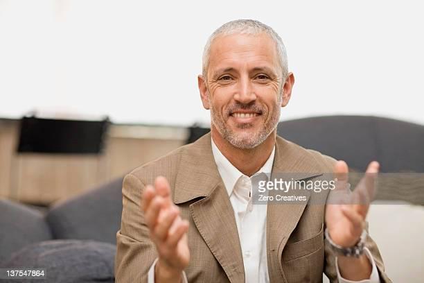 empresario sonriente hablando por un sofá - aplaudir fotografías e imágenes de stock