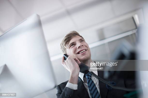 Smiling businessman talking on phone in office