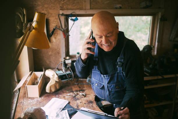 Smiling businessman talking on smart phone in workshop