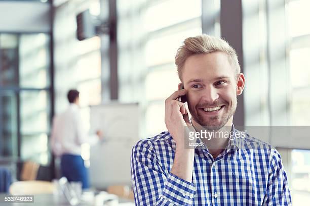 Smiling businessman talking on smart phone